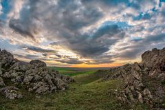 Beautiful landscape with green vegetation, rocks and a blue sunset sky with clouds. Dobrogea, Romania stock images