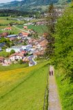 Beautiful landscape with Gruyeres city , fields and hiking coupl Stock Image