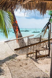 Beautiful landscape with hammock hanging on palm and boats in ocean on the background. Beautiful colorful landscape with hammock hanging on palm and boats in Stock Photo