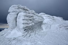 Beautiful landscape with high mountains, fog and gloomy mystical sky. Location place Carpathians. Rocks frozen with interesting textured frost and snow as if it stock photos