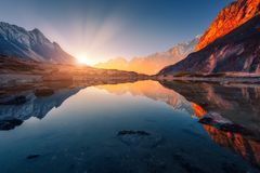 Mountains with illuminated peaks, stones in mountain lake at sunset Stock Images