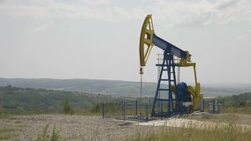 Beautiful landscape hills with pumpjack extracting oil  - stock footage