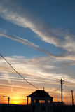 Beautiful landscape with house silhouette against the sky at sun. Set and power lines Royalty Free Stock Image