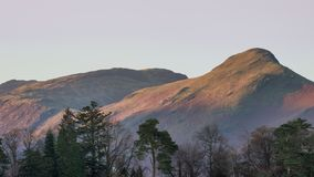 Beautiful landscape image of Catbells in Lake District hit by first light during Autumn Fall sunrise viewed from Derwent Water at