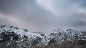 Beautiful Winter landscape image of Snowdonia National Park with. Beautiful landscape image in Winter of Snowdonia National Park with snow capped mountains in Royalty Free Stock Photography