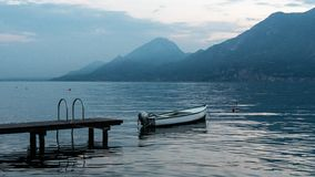 Beautiful landscape on lake Garda in Italy. Boat near the pier on the water surface of the water. The blue hues of the royalty free stock image