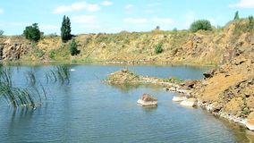 Beautiful landscape of lake in summer with basalt rocks, stones, calm water. Surface with dimples and green grass and ground forming a tiny peninsula stock video footage