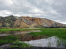 Beautiful landscape of Landmannalaugar geothermal area with river, green grass field and rhyolite mountains, Iceland royalty free stock photos
