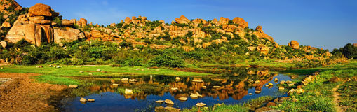 Beautiful landscape with large rocks near Hampi, India. Beautiful nature scenery with bright blue lake against the background of blue sky and strange landscape Stock Photo