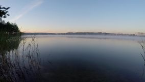 Beautiful landscape - morning haze moving across  pond. Beautiful landscape - morning haze spreads across the lake at dawn stock video footage