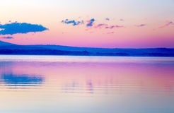 Beautiful landscape with mountains and lake at dawn in golden, blue and purple tones. stock photos