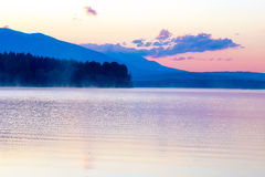 Beautiful landscape with mountains and lake at dawn in golden, blue and purple tones. Royalty Free Stock Photo