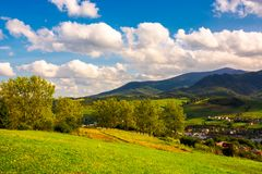 Beautiful landscape in mountains. Trees on the grassy hills of the Volovets serpentine. village at the foot of the mountain. lovely cloud formation over the Royalty Free Stock Photo