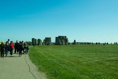 The path to Stonehenge - beautiful landscape. A beautiful landscape near Stonehenge with beautiful plantations of flowers and green grass. People walking from stock images