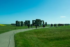 The path to Stonehenge - beautiful landscape. A beautiful landscape near Stonehenge with beautiful plantations of flowers and green grass. People walking from royalty free stock photo