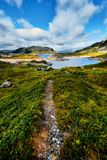 Beautiful landscape in Norway with a hiking trail leading through a valley with green grass and stones up to a blue lake in the mo Royalty Free Stock Photos