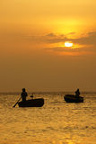 Beautiful landscape on ocean with silhouette of fisherman, sun a Stock Image