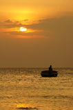 Beautiful landscape on ocean with silhouette fisherman, sun at s Royalty Free Stock Photos