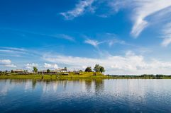 Beautiful landscape with an old village near river in wild Russia. stock photos