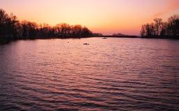 Beautiful landscape with orange sunrise, lake and fishermen Stock Photo