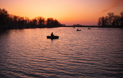 Beautiful landscape with orange sunrise, lake and fishermen Royalty Free Stock Images