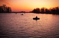Beautiful landscape with orange sunrise, lake and fishermen Stock Photography