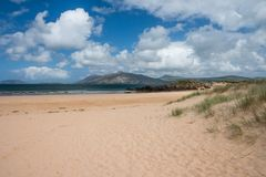 Beautiful landscape of Portsalon beach, Donegal, Ireland. Grass, sand dunes and fluffy clouds at Stocker Strand Royalty Free Stock Image