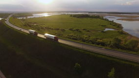 Beautiful landscape with a ride on the highway the trucks and a few cars at sunset. aerial view. Along the lake is the tracks on which rides a truck and a few stock video