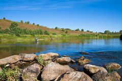 Beautiful landscape with river. Fishing in a rural location. Fishermen catch fish with bait. Summer season. Green vegetation along the banks. Blue sky, clear Royalty Free Stock Image