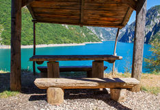 Beautiful landscape with river or lake and mountains view. Place for getting rest in recreation area. Picnic table. Stock Image