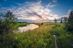 Landscape of the riverbank at sunset with the sun above the horizon stock image