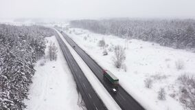 Beautiful landscape with road and conifer forest on snowy winter day aerial view.