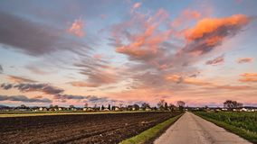Beautiful landscape with road, fields and blue sky covered partially with fluffy colorful clouds in the background. Austria, Styria stock photo