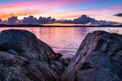 Nature Landscape with Boulders by Fjord and Dramatic Sky at Beautiful Sunset. Beautiful landscape with rocks, fjord and colorful clouds at dramatic sunset stock photo