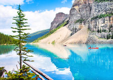 Beautiful landscape with Rocky Mountains and mountain lake in Alberta, Canada. Beautiful landscape with Rocky Mountains and tourists canoeing on azure mountain royalty free stock image
