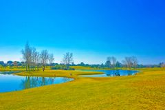 Beautiful Landscape Scenery with Rough Pastels Filter, Golf Course, Bright Blue Sky, Sunny Day, Small Lakes and Trees royalty free stock images