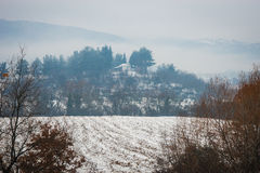 Beautiful landscape with small house on  hill, snow and fog Royalty Free Stock Photo