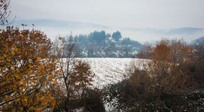 Beautiful landscape with small house on  hill, snow and fog Royalty Free Stock Images
