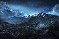 Beautiful landscape snow mountains at night on blue cloud and star background. Leh, Ladakh, IndiaDouble Exposure. Beautiful landscape snow mountains at night on stock image