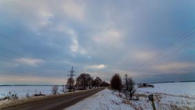 Beautiful landscape on a snowy field near a lonely road. Daily timelapse. Beautiful lush clouds float over a snowy field. stock video