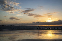 Beautiful landscape Summer sunset sky reflected on wet beach at Royalty Free Stock Images