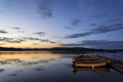 Beautiful landscape sunrise over still lake with boats on jetty Stock Photos