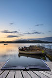 Beautiful landscape sunrise over still lake with boats on jetty Stock Image