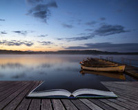 Beautiful landscape sunrise over still lake with boats on jetty Stock Photo