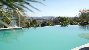 Beautiful landscape with swimming pool, palms and mountains on the background