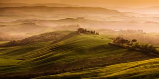 Beautiful landscape in Tuscany in Italy with fog during sunrise and hills in the background and green fields. And a farm on the hilltop royalty free stock images