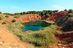 Bauxite Lake Cave near Otranto, Italy. The lake in a old bauxite's red soils quarry cave in Apulia, Otranto, Salento, Italy. The digging was filled with Royalty Free Stock Photo