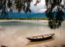 Beautiful landscape in Vietnam. A beautiful vietnamese landscape with a wooden boat reflecting in the tranquil waters. of a bay. Point of view is under the Stock Images