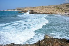 Beautiful landscape view of big waves and a rocky beach of Crete. Big waves of the blue sea captured from the coast in a beach of Crete Royalty Free Stock Photography