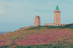 Vintage Cap Fréhel. Beautiful landscape view of the cliffs at Cap Fréhel in Brittany, France, with its lighthouses and moorland with vibrant heather flowers Royalty Free Stock Photo
